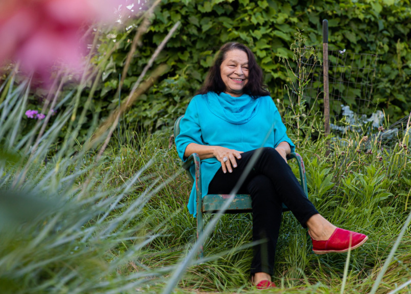 A Native American woman sits in a rusted metal chair in a wooded, grassy setting. She wears a loose-fitting bright blue shirt, black pants, and red loafers; she smiles brightly and looks to the left of the camera, her hands resting casually on her legs.