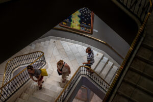 Photo looking down through a spiral staircase of the museum; three young adults are making their way up the stairs.