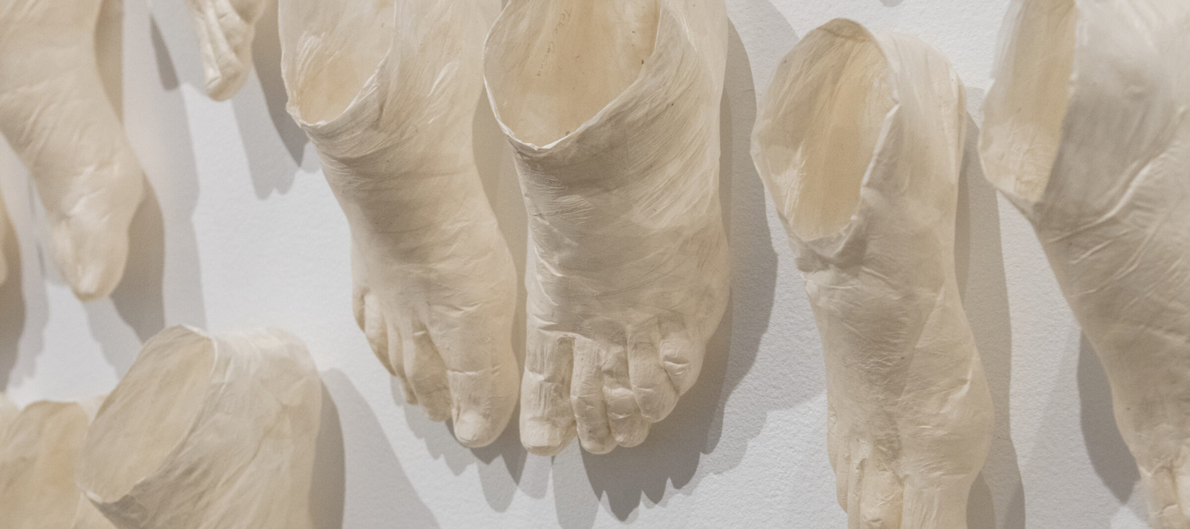 Detail view of a contemporary art installation made up of countless beige foot sculptures that extend from the walls onto the dark floor. The feet are in pairs in varied sizes and staggered as if moving. Marks on the sculptures indicate the folds of human skin and bone.