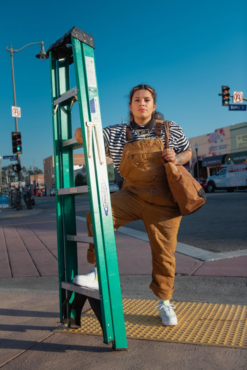 A woman wearing camel colored overalls stands on a city street corner, one arm holding a shoulder bag and the other rm and leg holding a tall green ladder vertical.