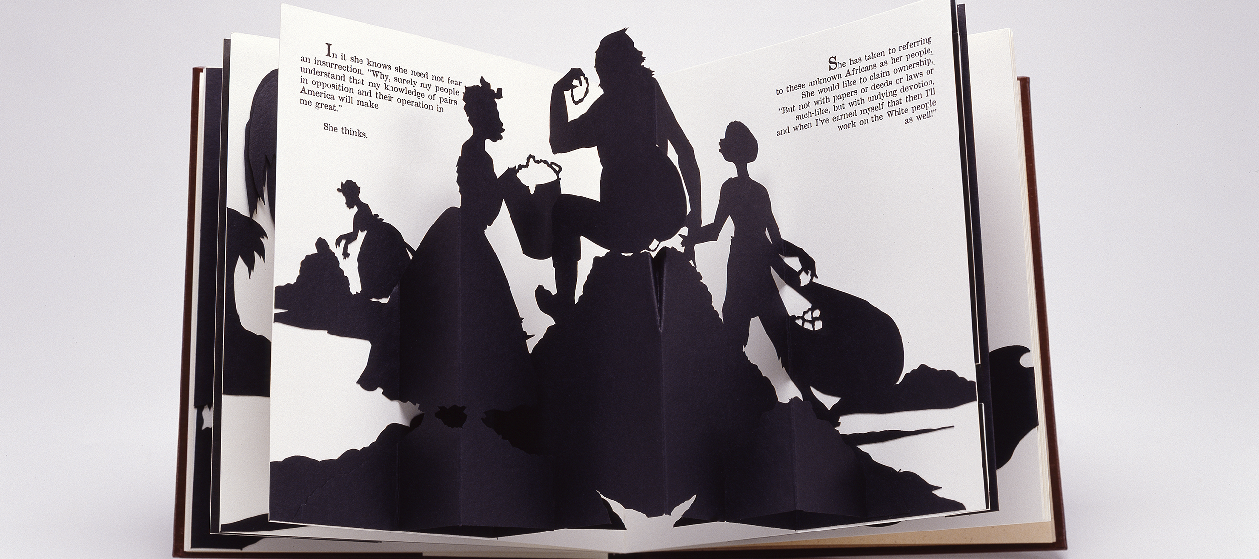 Four black silhouetted figures emerge from the white, open pages of a pop-up book. They appear to be engaged in manual labor. Two of the figures wear full floor-length skirts.