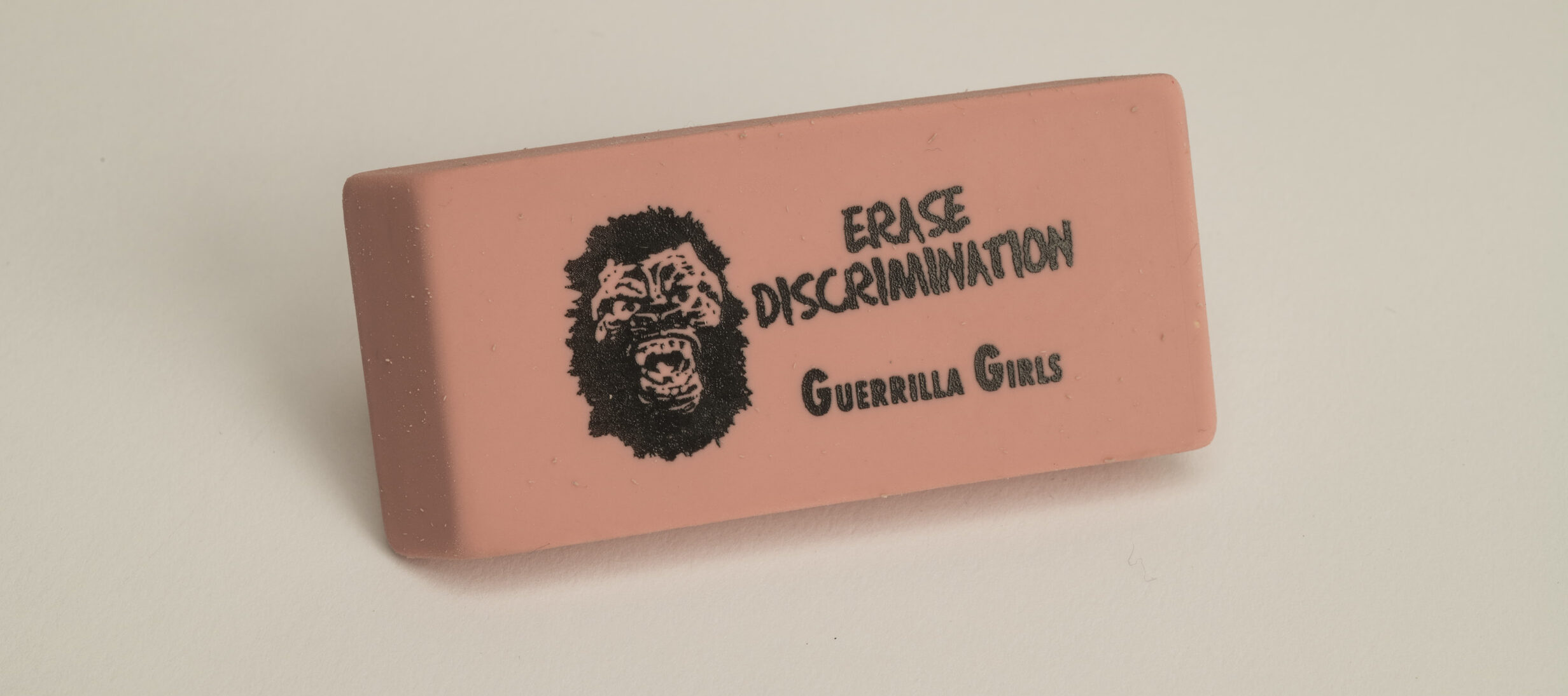 A rectangular pink eraser against a white background. Printed on the eraser in black is a yelling gorilla face to the left of the words,