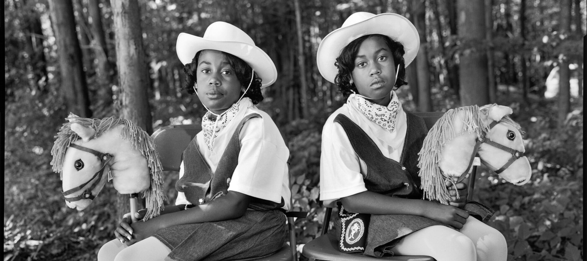 A black and white photograph of two black teens sitting in folding chairs, facing the camera with their bodies angled in opposite directions. They wear matching cowboy hats, bandanas around their necks, vests, white tights, and white western-style boots. They hold two white hobby horses in their hands. In the background are trees and a forest.