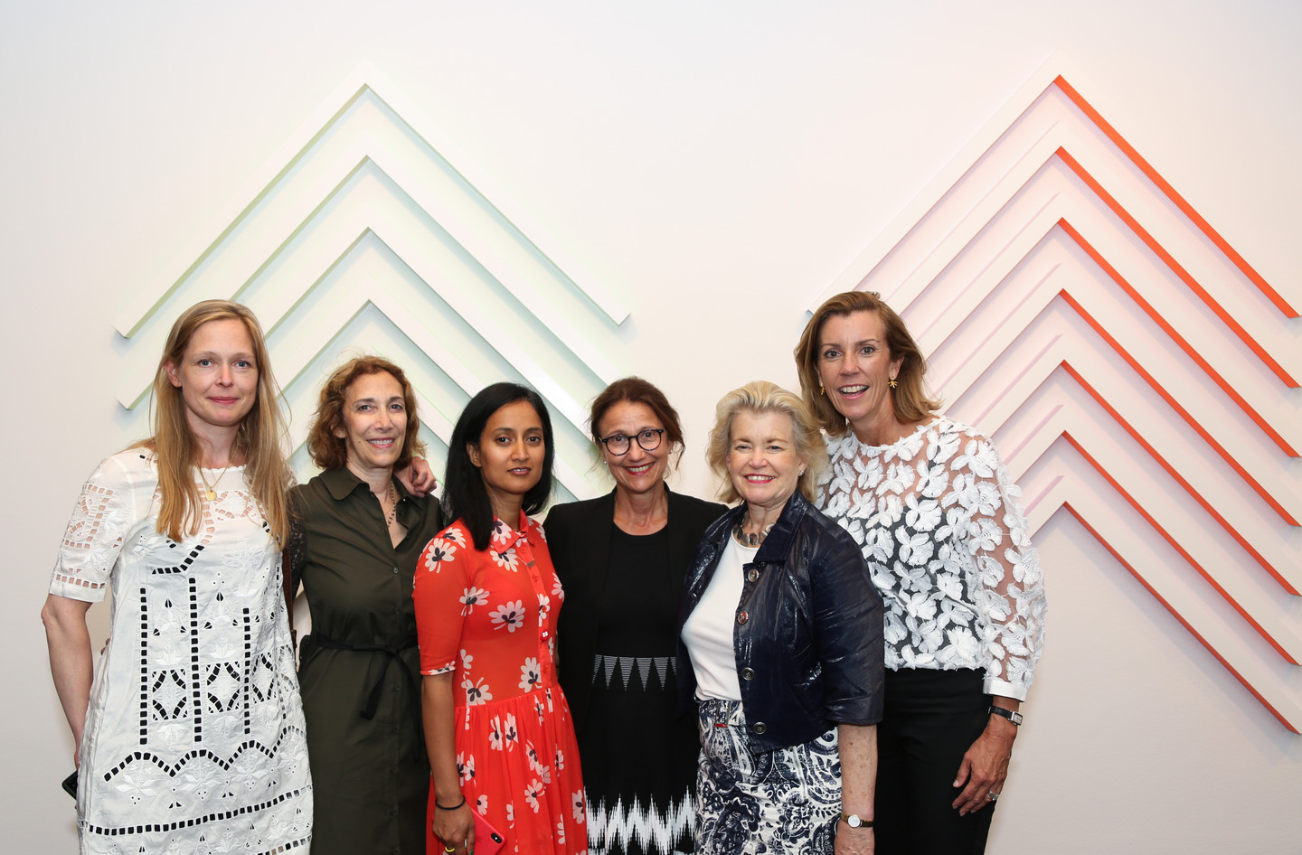A photograph of a group of five light-skinned women and one medium-skinned woman dressed in cocktail attire stand in front of a geometric wall sculpture.
