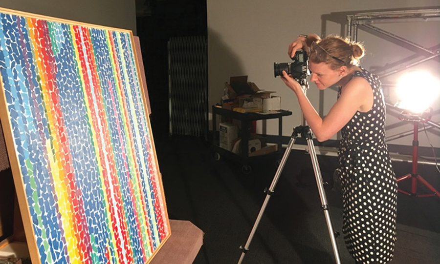 A light-skinned woman with blonde hair wearing a sleeveless polka-dot dress stands in a dark gallery behind a camera and tripod. She photographs an abstract painting composed of brightly colored, lozenge-shaped brushstrokes in vertical stripes of rich blue, purple, turquoise, yellow, orange and red.