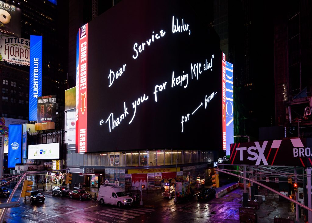 "In Times Square, New York City, a large digital billboard features a black background and white handwritten text that says ""Dear Service Worker, Thank you for keeping NYC alive!"" for ---> forever..."