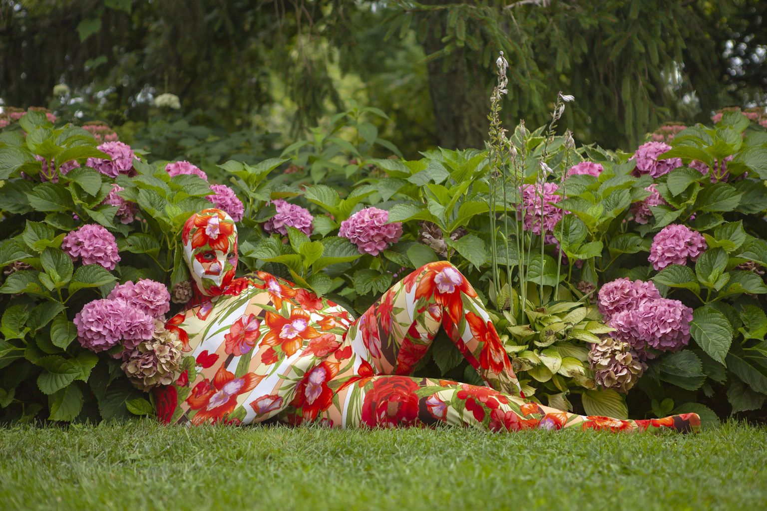 A figure wearing a tight body suit and head mask covered in a red and pink floral print reclines in cut grass, in front of blooms of purple flowers. Only the eyes of the figure are visible.