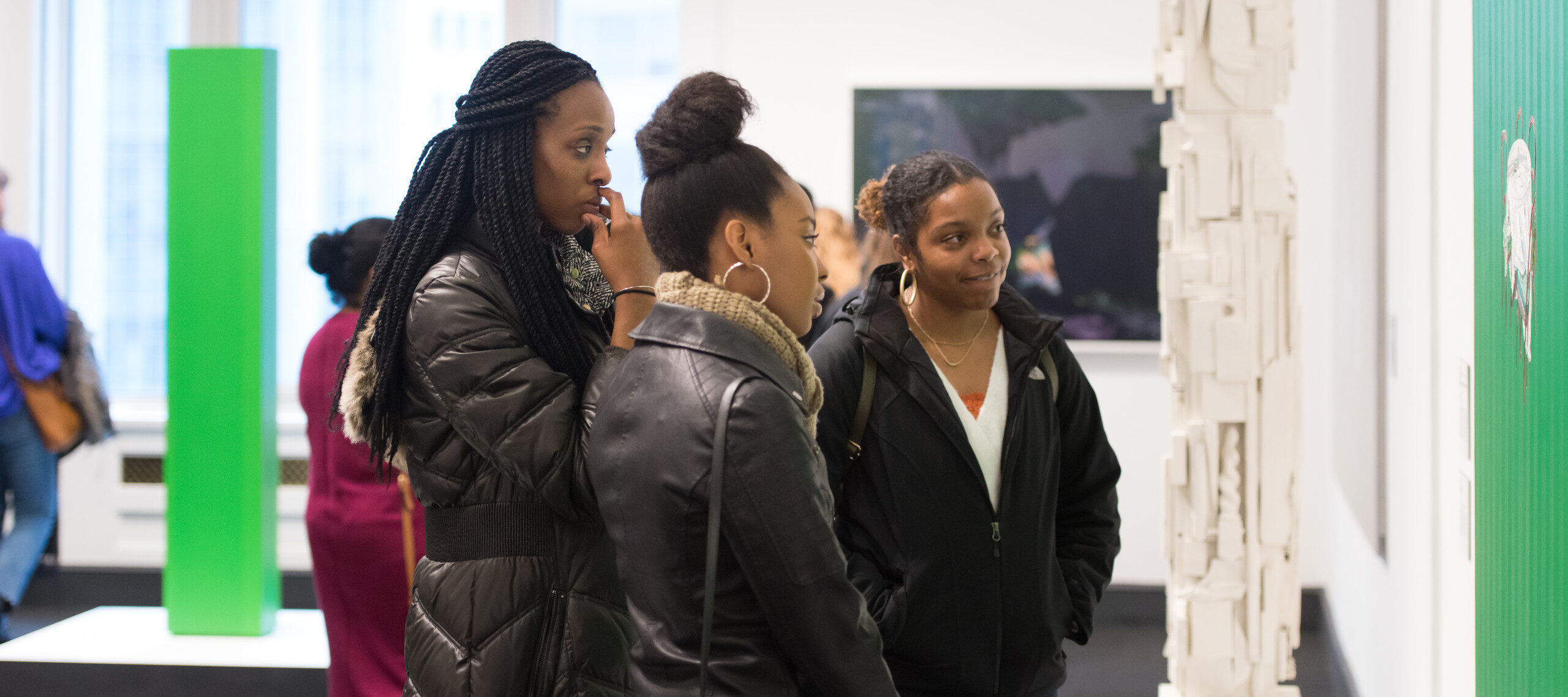 Three dark-skinned young adults in winter jackets stand in an art gallery near a white pillar made of a medley of found items. They wear black winter jackets and smile at the artwork.