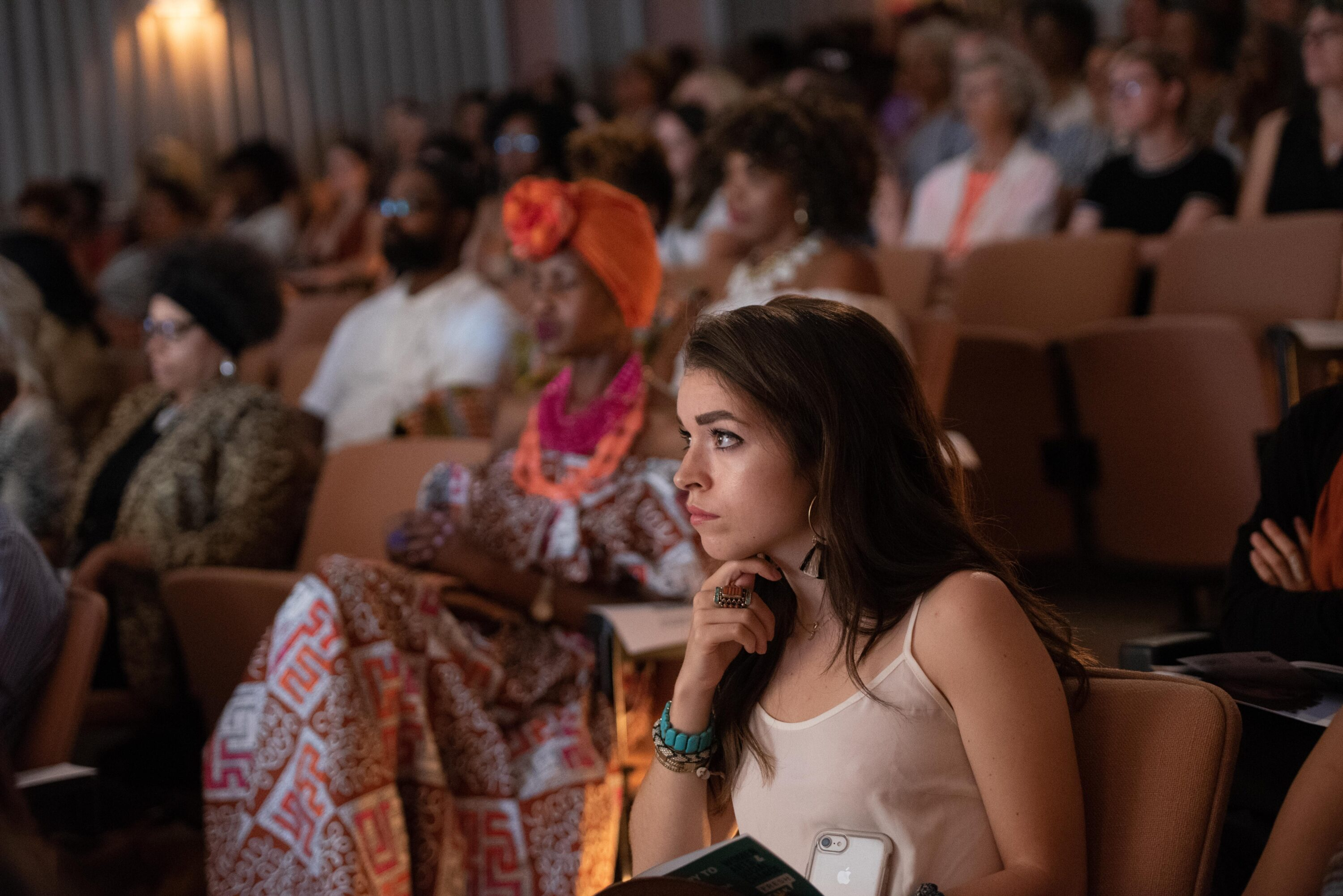 An audience seated in a dim theater looking intently forward. Focused in the foreground is a light-skinned person with their chin on their hand, long brown hair, and a tank top.