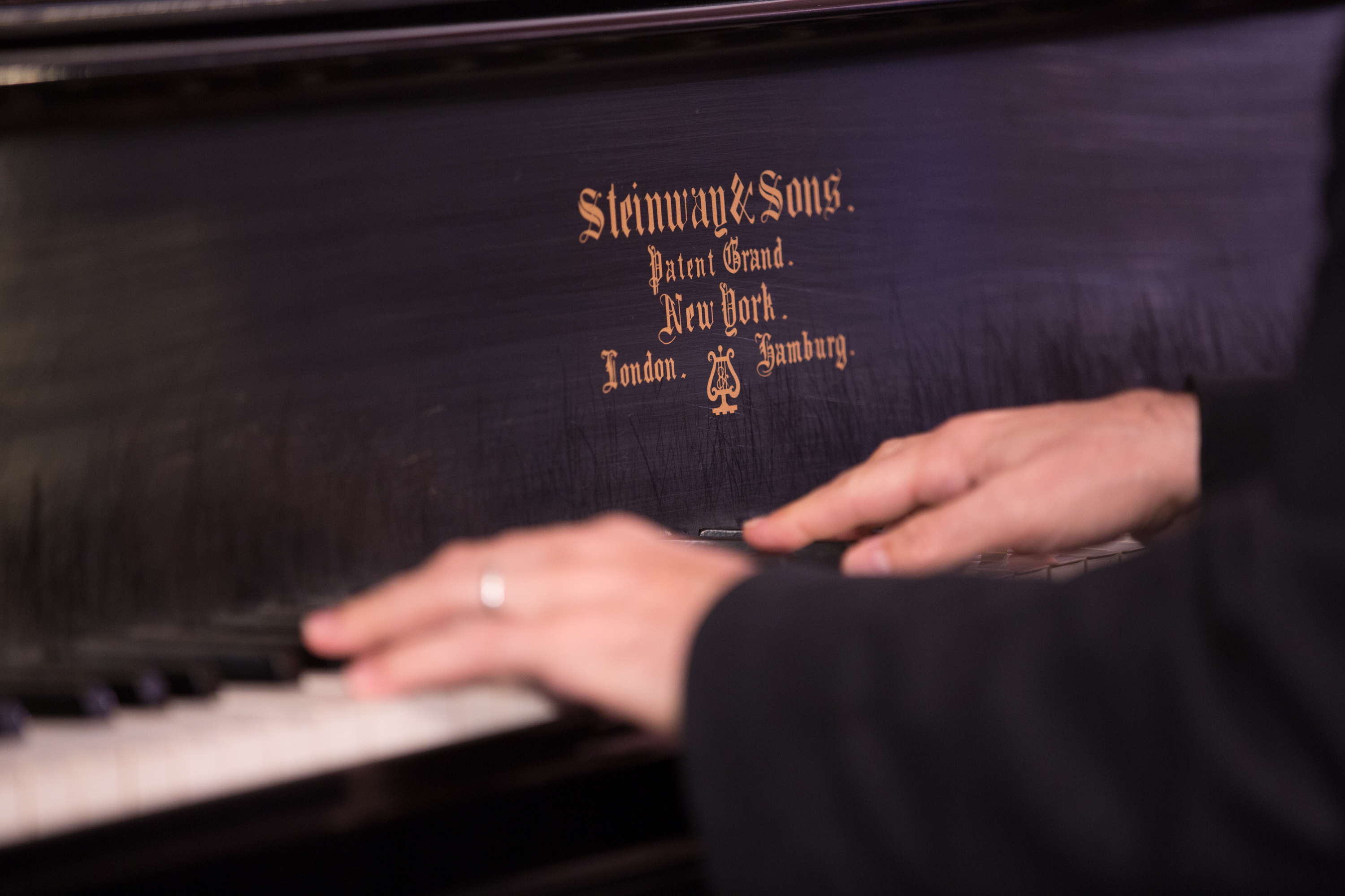 Two light-skinned hands in the middle of playing a black-and-white piano keyboard.