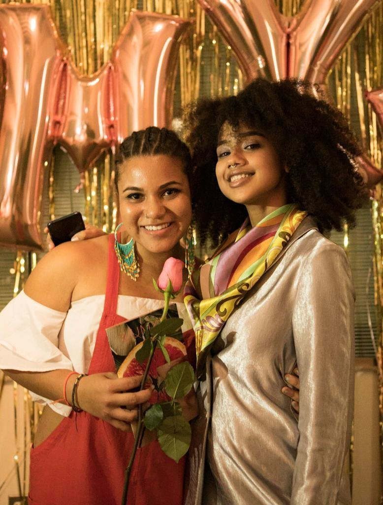 Two dark-skinned women lean close together and smile at the camera in front of shiny rose gold balloons and gold fringe streamers. The woman on the left holds a pink rose and a book that features a photo of a grapefruit half. She has her arm around the waist of the woman on the right, who wears a velvety blazer and pastel patterned scarf.