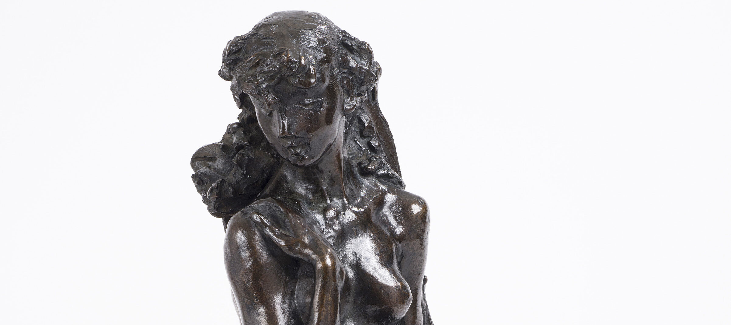 Bronze tabletop sculpture depicting a nude young woman seated on rough-hewn base, leaning against a sheaf of wheat. The figure's knees are drawn together, her left arm hanging at her side and her right arm bent upwards, clasping her shoulder.