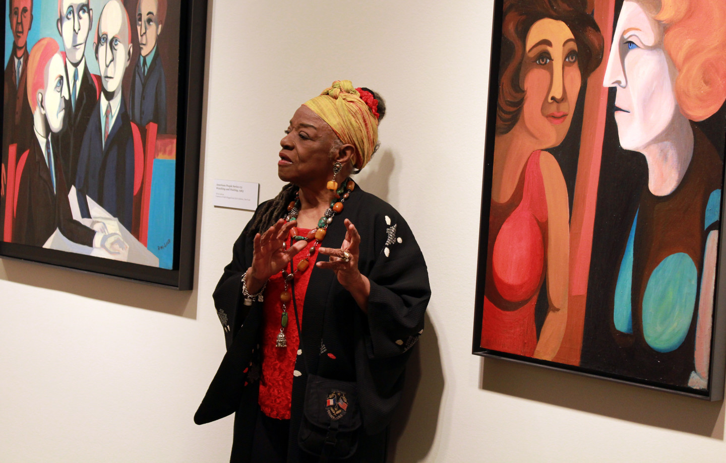 Faith Ringgold stands and speaks, gesturing with her hands, in front of her portrait paintings. She is a dark-skinned adult woman wearing colorful clothing and a black sweater, including a yellow head wrap and chunky jewelry—rings, earrings, necklaces, and bracelets.