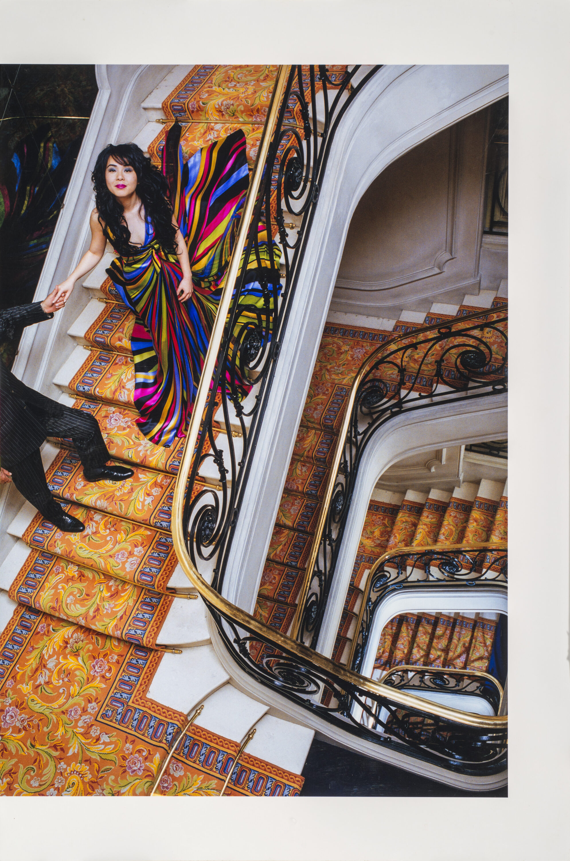 A bird's eye view of a woman with long, dark hair in a brightly-colored gown descending an ornate spiral staircase of white marble and colorfully patterned rug. Her right hand is being held by a figure in a black suit whose head and shoulders are cropped out of the image.