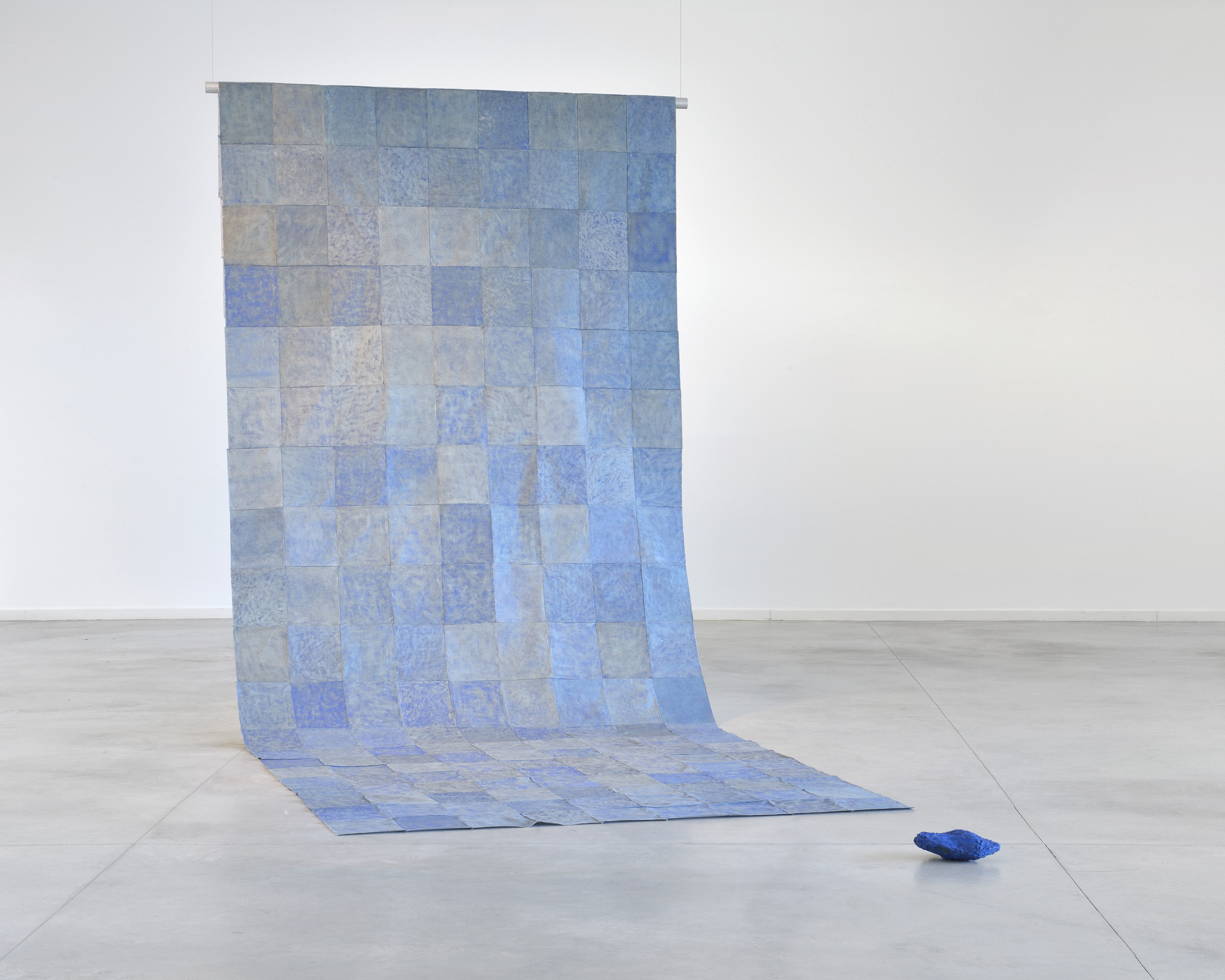 A floor to ceiling contemporary installation of blue square sheets patched together into a long panel that hangs down from two wires and partly rests flat on the floor. A dark blue object lays nearby.