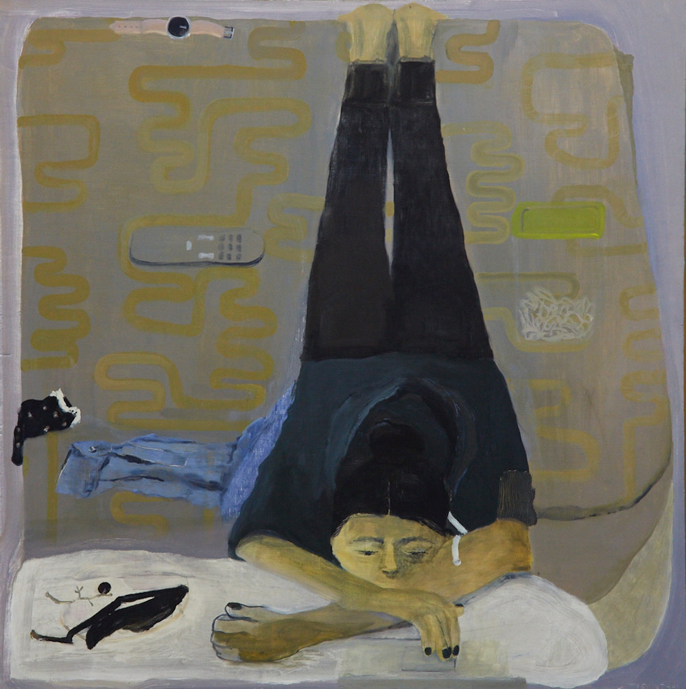 On a grey and yellow bedspread lies a sulking woman with medium skin, her body contorted with her shoulders tense, arms crossed, and legs hyperextended. With her chin on a white body pillow, she stares forward into nothingness while wearing all black.