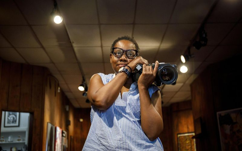 An African American woman with short cropped hair and black-framed glasses holds a large camera to the right of her face. The room she is in is dimly lit and wood-paneled.