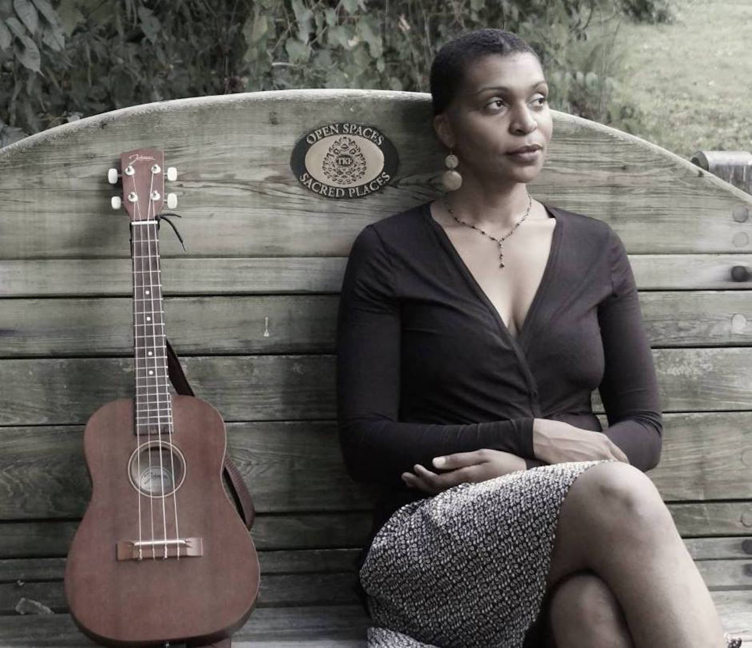 Courtney Dowe sits on a wooden bench with a high back with a standing brown guitar on her right. Her legs are crossed and her arms are crossed on her lap. She wears a black top, a patterned skirt, earrings, and a necklace, and she has very short hair. Behind her is lush greenery.