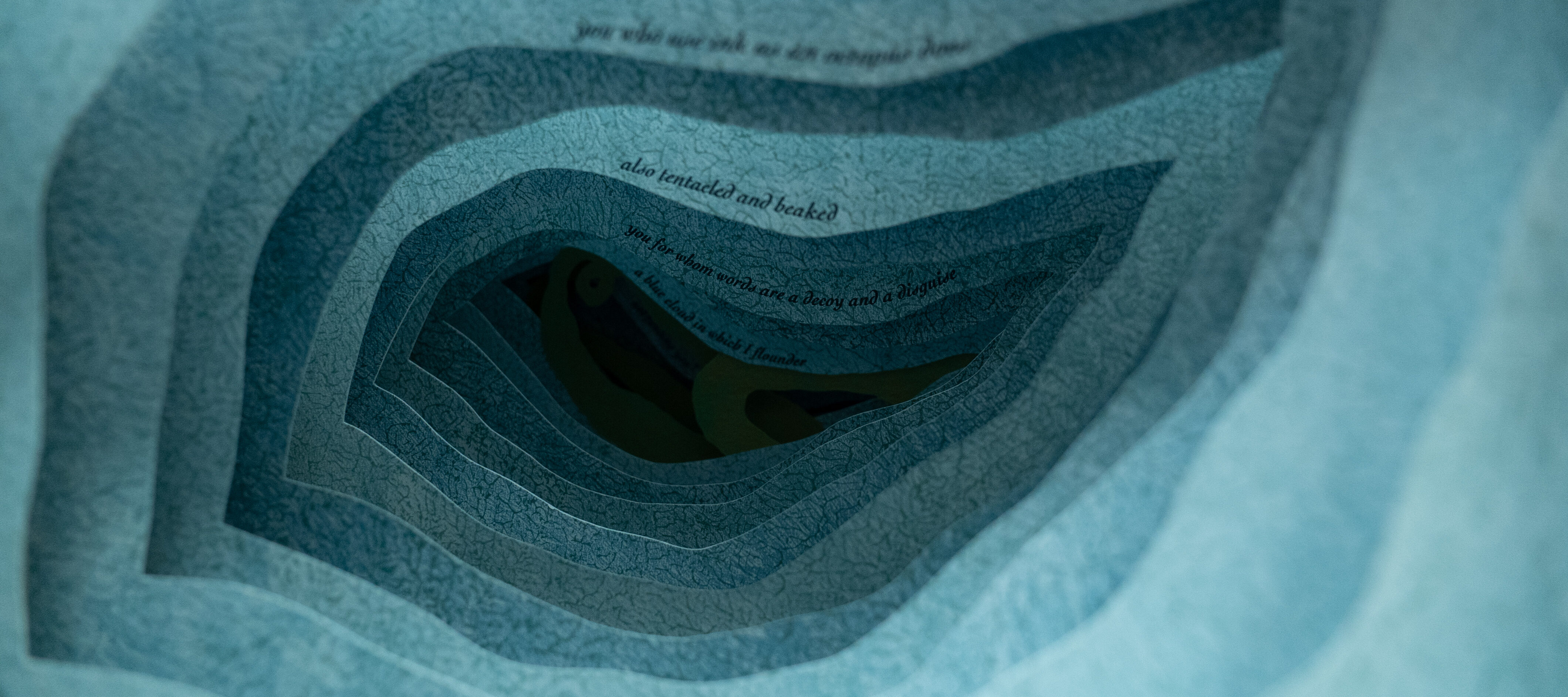 A close up photograph of an artist's book. Each layer of blue paper has an organic, irregular shape cut out of the middle so the layers form a tunnel. A line of text is printed in small type on each page, receding into the tunnel like an underwater cavern.
