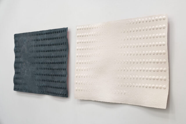 An oblique view of two side-by-side sheets made of pulp, one black and one pale pink. They both have raised surface patterns in the shapes of moon phases. Red paint on the back of the sheets reflects a sliver of color on the walls.