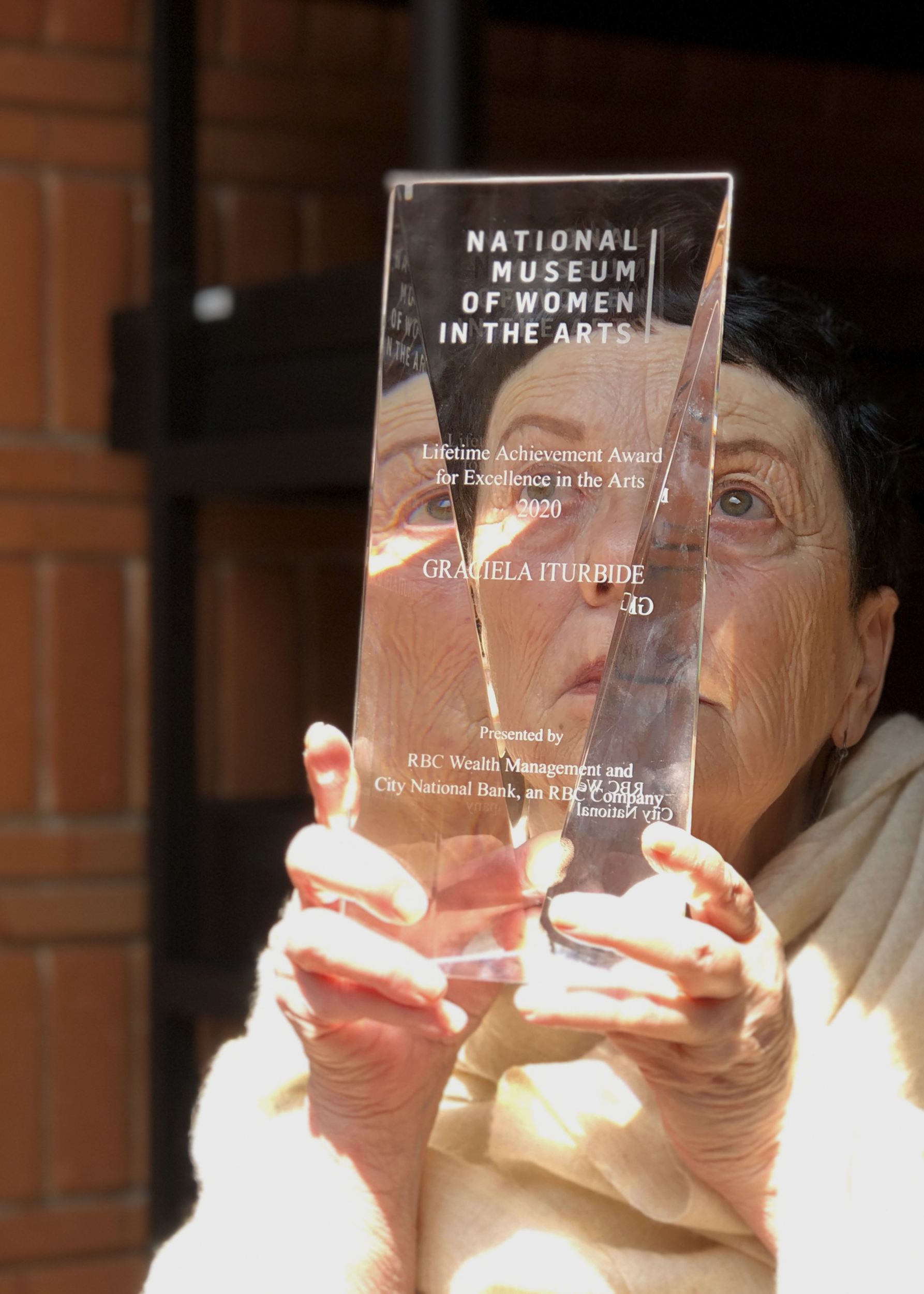 A light-skinned older woman with brown cropped hair holds a clear rectangular award up to her face, so that half of her face is visible through the award; sunlight streams in on the woman's face and hands.