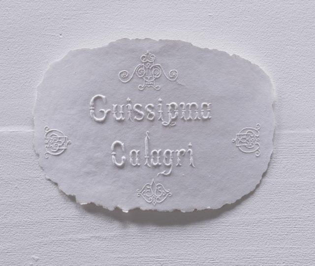 The name 'Guissipina Calagri' is inscribed in a stylized typeface and slightly raised off the surface of a thin white paper pulp base with frayed edges.