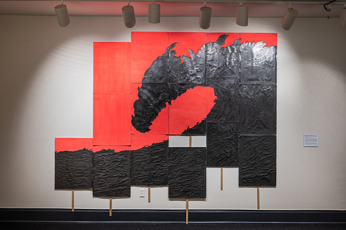 Six rectangular panels of varying heights with a coral background are hung together on a wall with yardsticks attached to the bottoms of each panel. Each panel includes a part of a textured graphite drawing that looks like a giant crashing wave when seen as a whole.