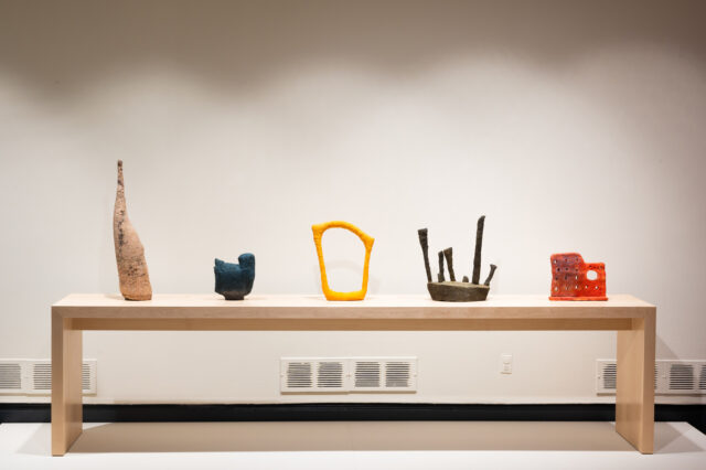 An installation view of five different colored abstract contemporary sculptures sitting in a line on a long light wood rectangular table that is on a low white platform.