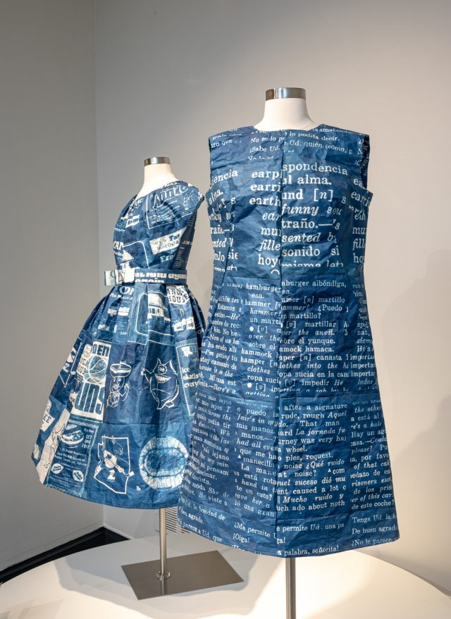 A sleeveless rich blue short dress is placed on a headless white dress form. The dress has white texts printed on the surface. Behind it is another, similar dress with short sleeves and belt.