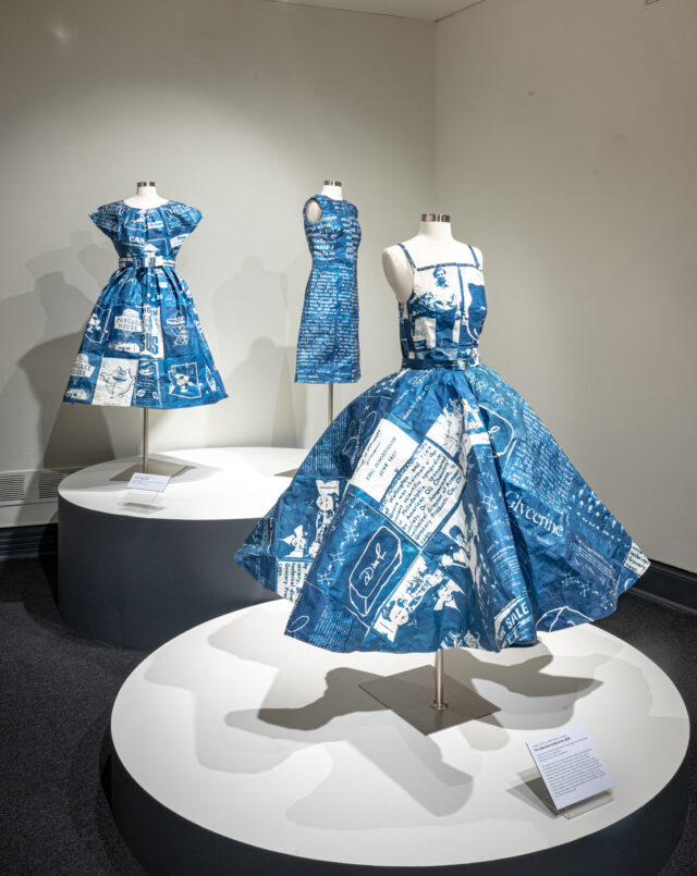 A group of three rich blue and white dresses placed on a headless white mannequin on rounded pedestals. The dresses are printed with imagery and text.