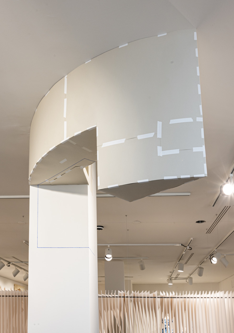 Beige paper geometric construction anchored to the ceiling and white square column