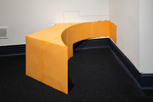 An orange geometric abstract sculpture with varied angles positioned against a corner on the floor. The sculpture has painted lines extending onto the walls.