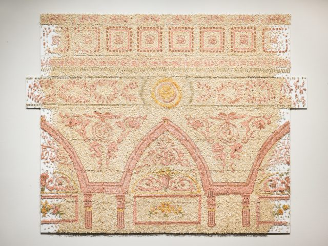 A large contemporary art installation of a decorative architectural cornice made of countless pink and yellow cut paper insects.
