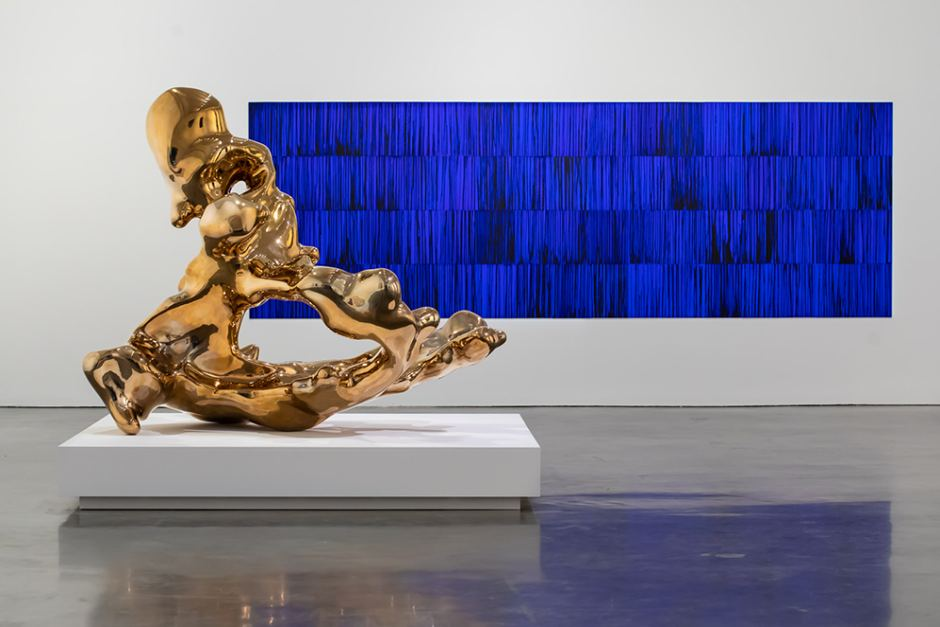 On the left, a large, gold metallic abstract sculpture reflects the light of the gallery. The sculpture is an uneven liquid bronze triangle with a hole in the middle. In the background sits a wide rectangular painting of blue and black upward brush strokes.