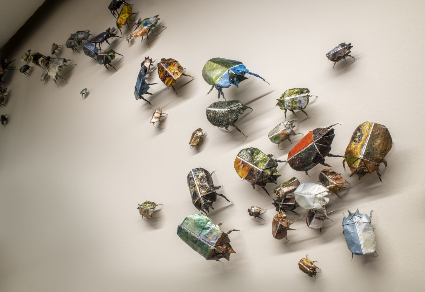 Detail of installation of origami beetles of different colors, designs, and sizes in varied positions on a wall.