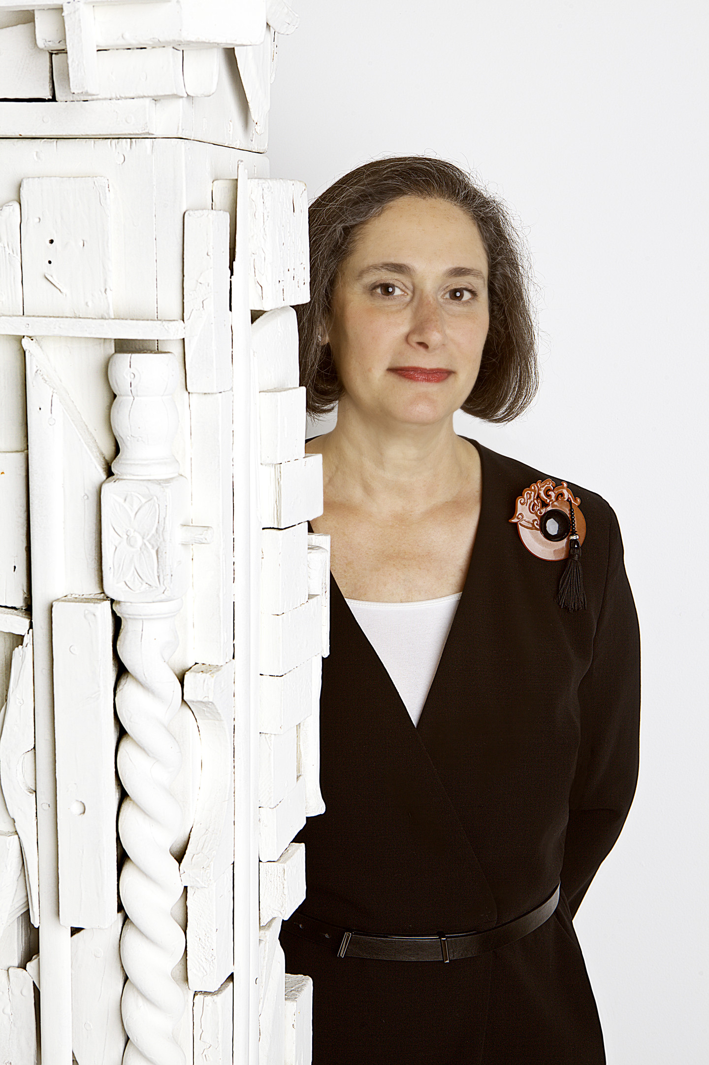 A woman with light skin and short brown hair posing behind a white assemblage sculpture.
