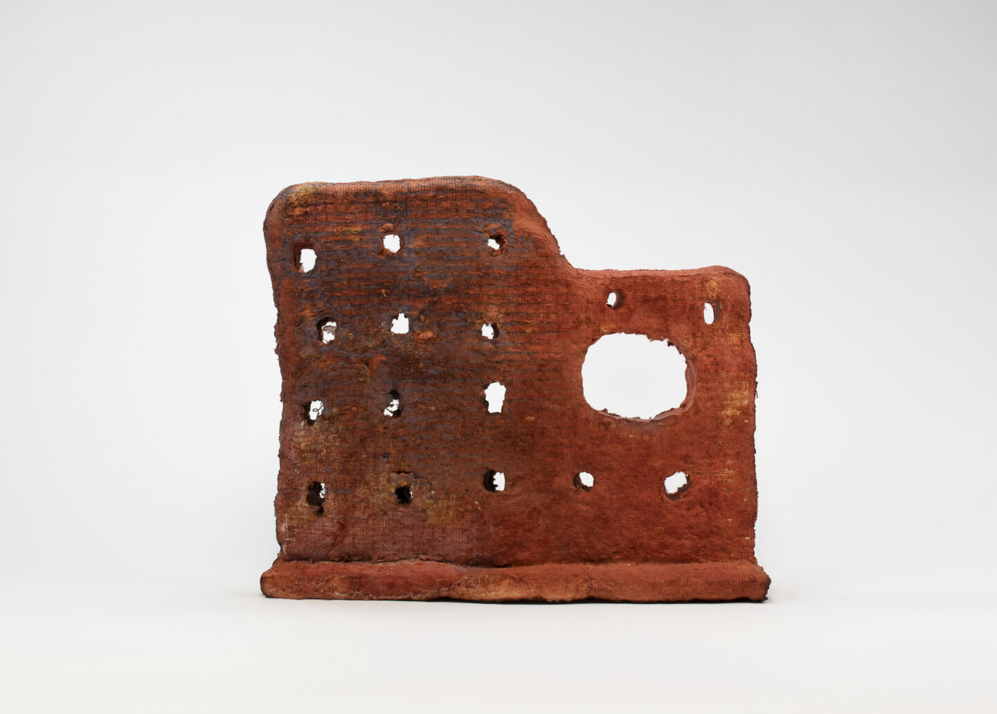An irregular shaped red abstract sculpture that looks like the side wall of an old building structure. Rows of holes and one bigger void space cover the surface of the grainy, rough sculpture.