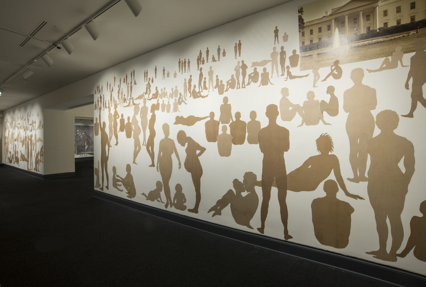 A long rectangular wall with many silhouetted figures made out of brown Kraft paper. The figures are of men, women and children in different positions as if in a landscape. They are different sizes to indicate foreground, middle ground and background. A sepia-toned photograph of the White House at the upper right corner.