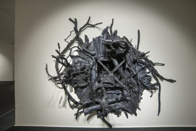 A contemporary black wall sculpture in a rounded shape with many twisted branches protruding out from the work. A void space is in the center.