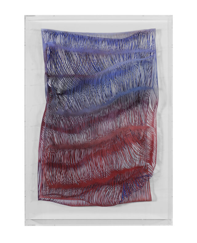 A rectangular paper work in a plexiglass box that shows thousands of slashes through the work to create waves and shadows throughout the surface. The color shifts from purple at the top to blue to red at the bottom.