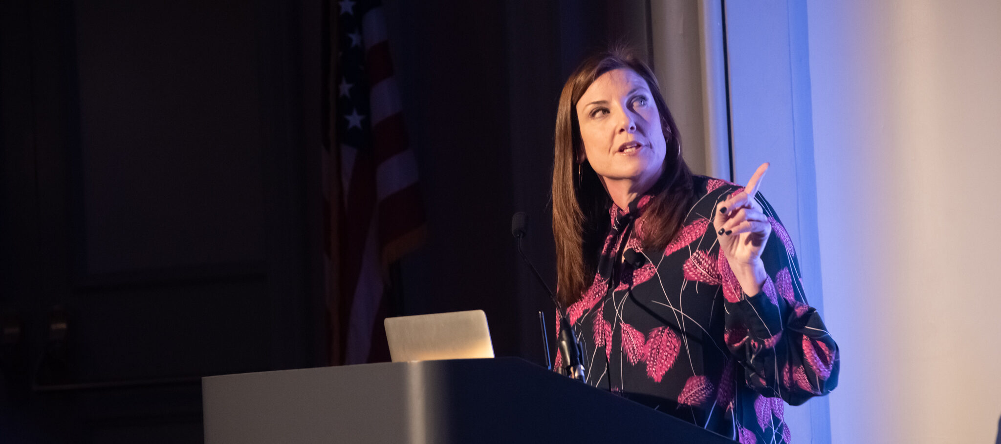 Jackie Payne—a light-skinned adult woman with straight, dark brown hair—stands at a podium in front of a laptop, looking to her side and behind her at a projected presentation she's giving. Her left hand is raised to point at the presentation while she speaks.
