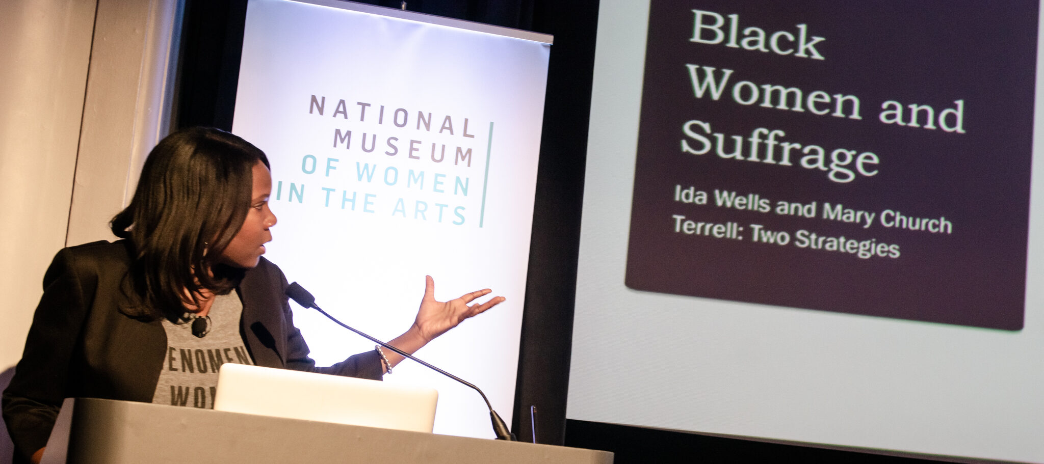 "Adjoa B. Asamoah—a dark-skinned adult woman—stands at a podium with the NMWA logo on the front. She speaks into a microphone while gesturing at a projected presentation slide behind her that reads ""Black Women and Suffrage. Ida Wells and Mary Cherch Terrell: Two Strategies."""