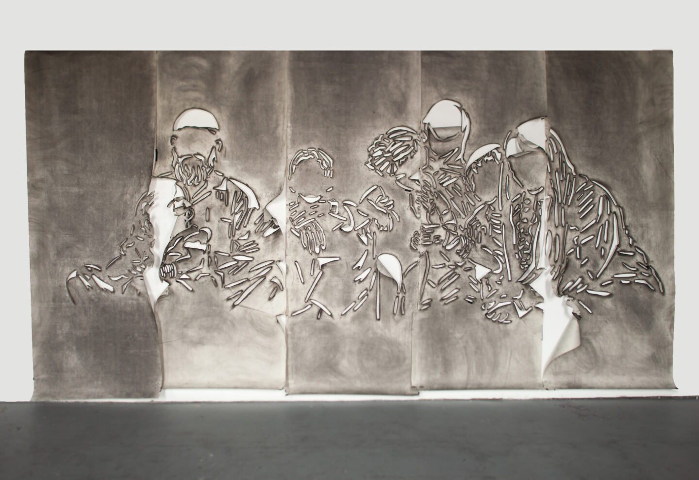 Five panels of paper covered in gray charcoal in which there is a cut stencil of an image of a group of faceless people. The panels have portions of paper that flap and fold.