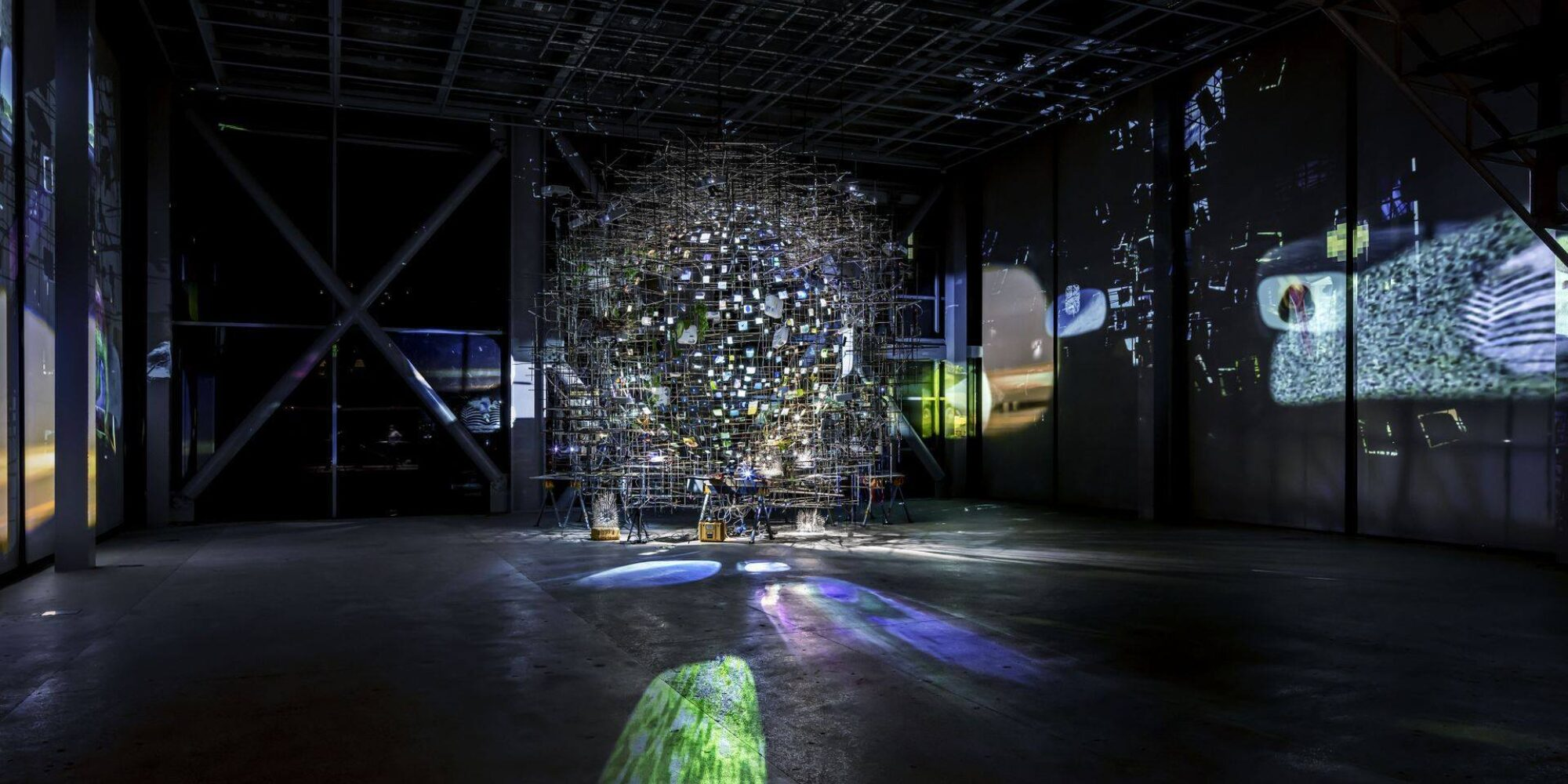 In a black gallery stands an orb-like structure of many small lights surrounded by scaffolding. Large projections of blue and white light project onto the floor, and scenes play on the left and right wall.