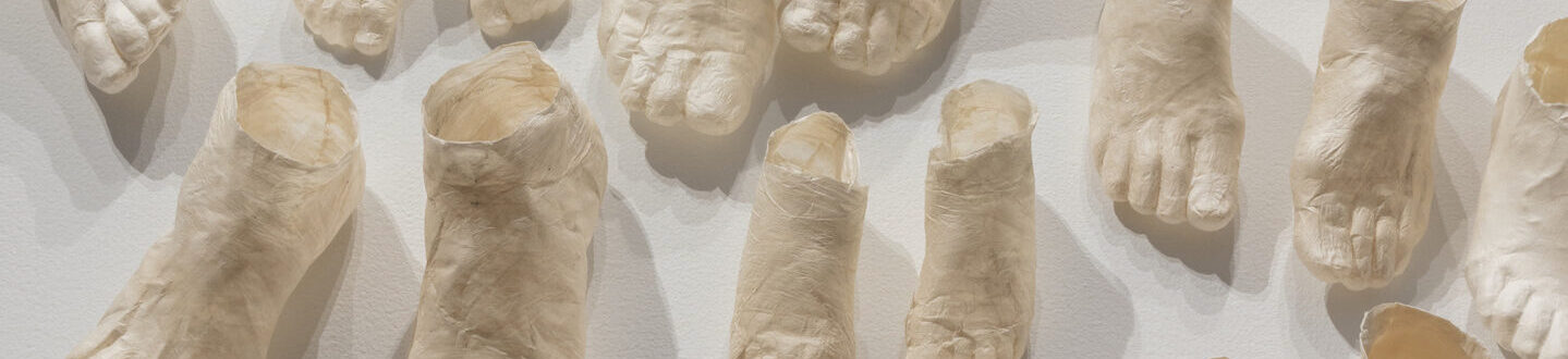 Dozens of pale, hollow, ghostly feet of different sizes made of translucent paper arrayed in pairs on a white background.