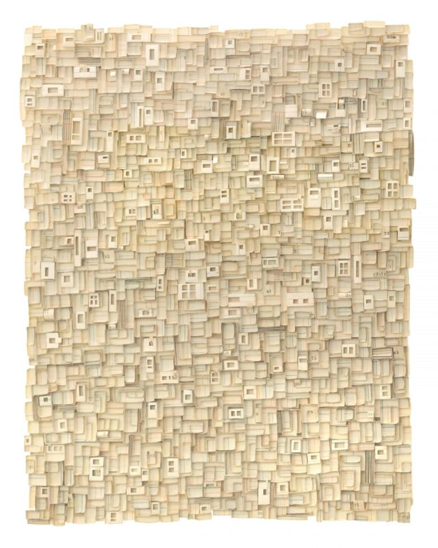 A beige rectangular work with fragments of small boxlike elements adhered together to create a textured surface.