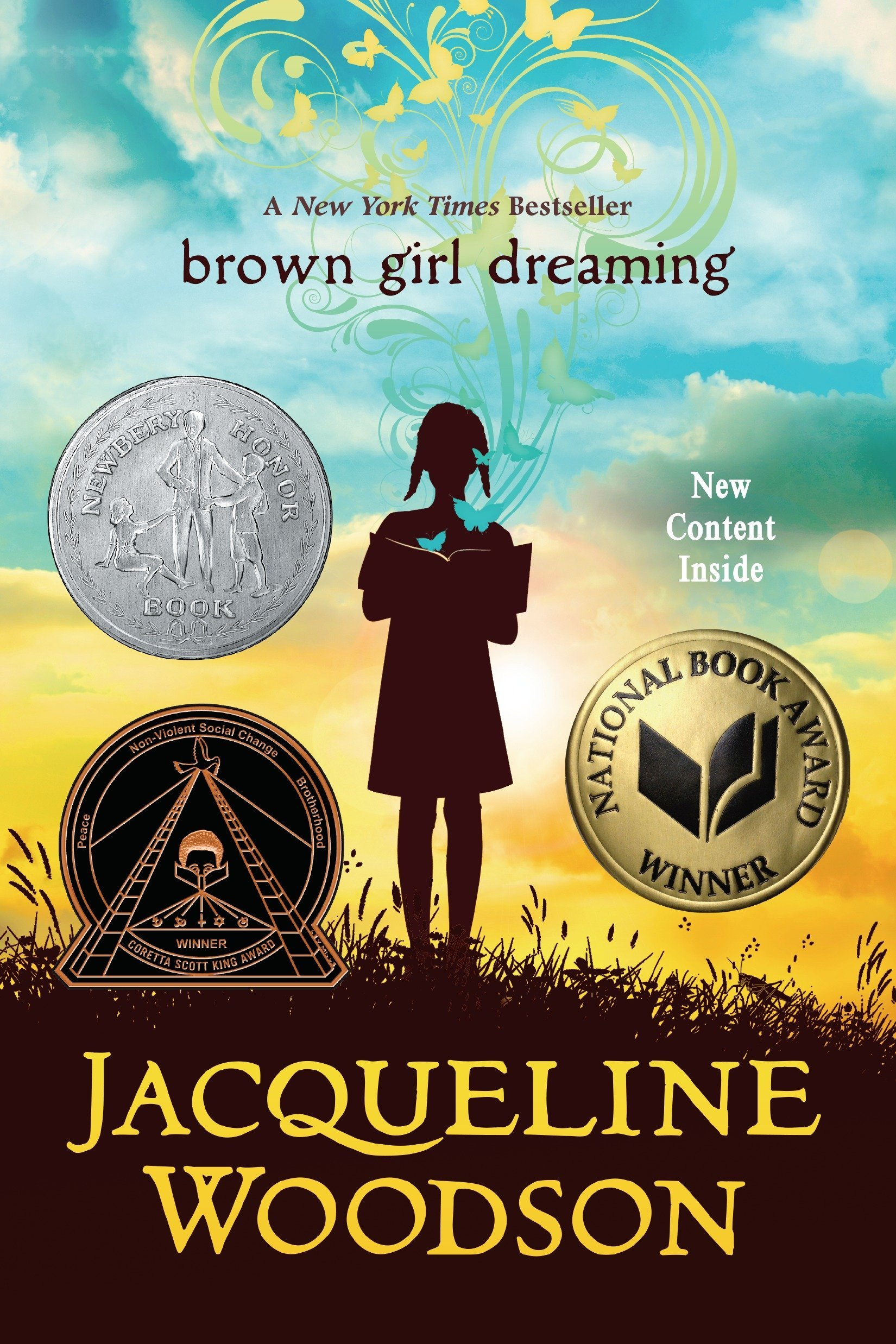 """A book cover featuring the title """"brown girls dreaming"""" in brown letters over a blue and white clouded sky. The silhouette of a young girl reading a book is positioned in the middle of the cover, in front of a golden sky. Three medals of honor surround her."""
