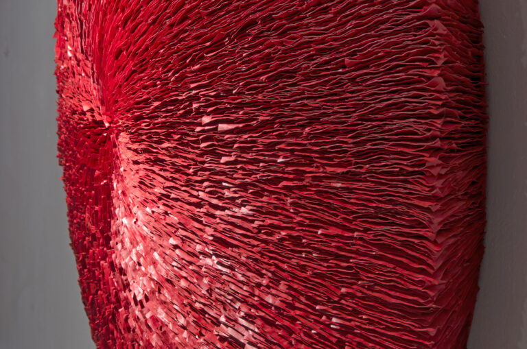 An oblique view of a deep red abstract round wall sculpture made from stacks of paper. Surface is highly textured with lines radiating outwards from the center.