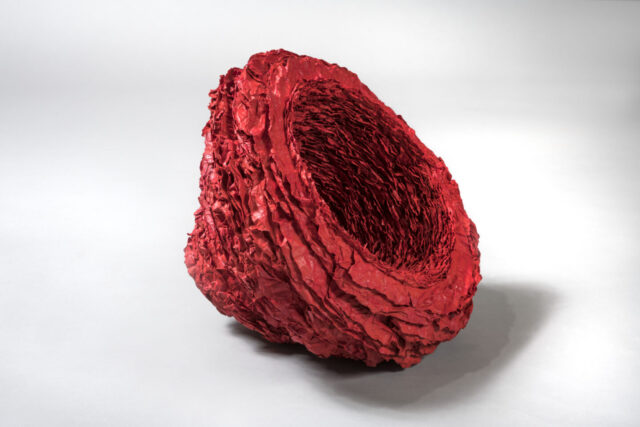 Side view of a deep red abstract round sculpture made from stacks of paper. Surface is highly textured with lines radiating outwards from the center.