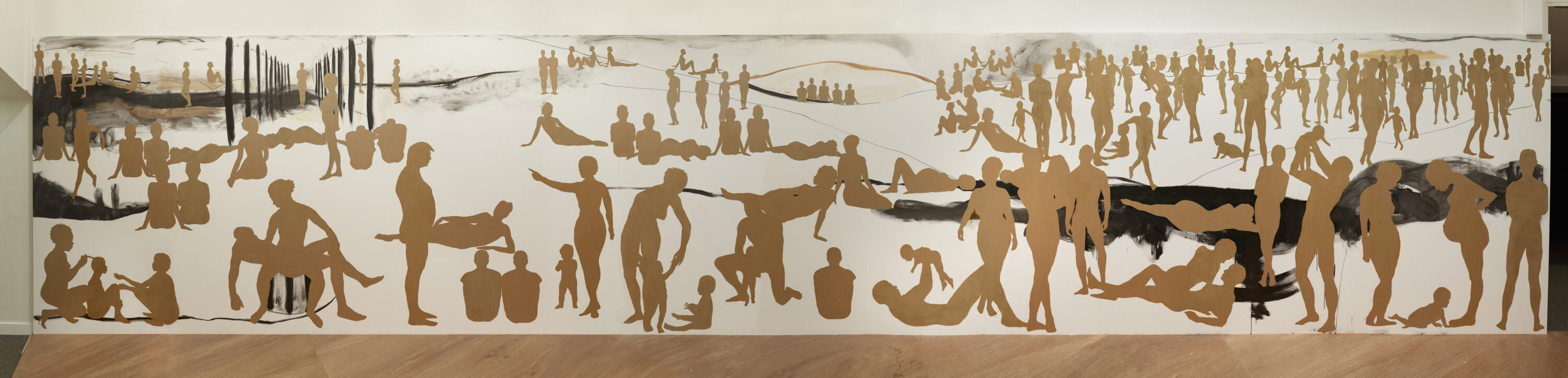 A long rectangular wall with many silhouetted figures made out of brown paper. The figures are of men, women and children in different positions as if in a landscape. They are different sizes to indicate foreground, middle ground and background.